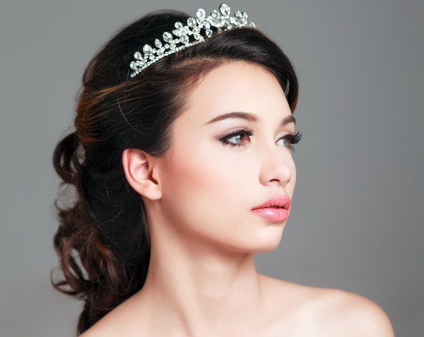 "alt=""Young bride with tiara modeling beautiful bridal hair style and makeup"""